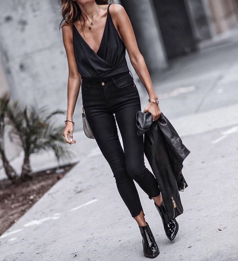 Black Wrap Top And Black Skinny Jeans With Glossy Black Boots For Spring 2020
