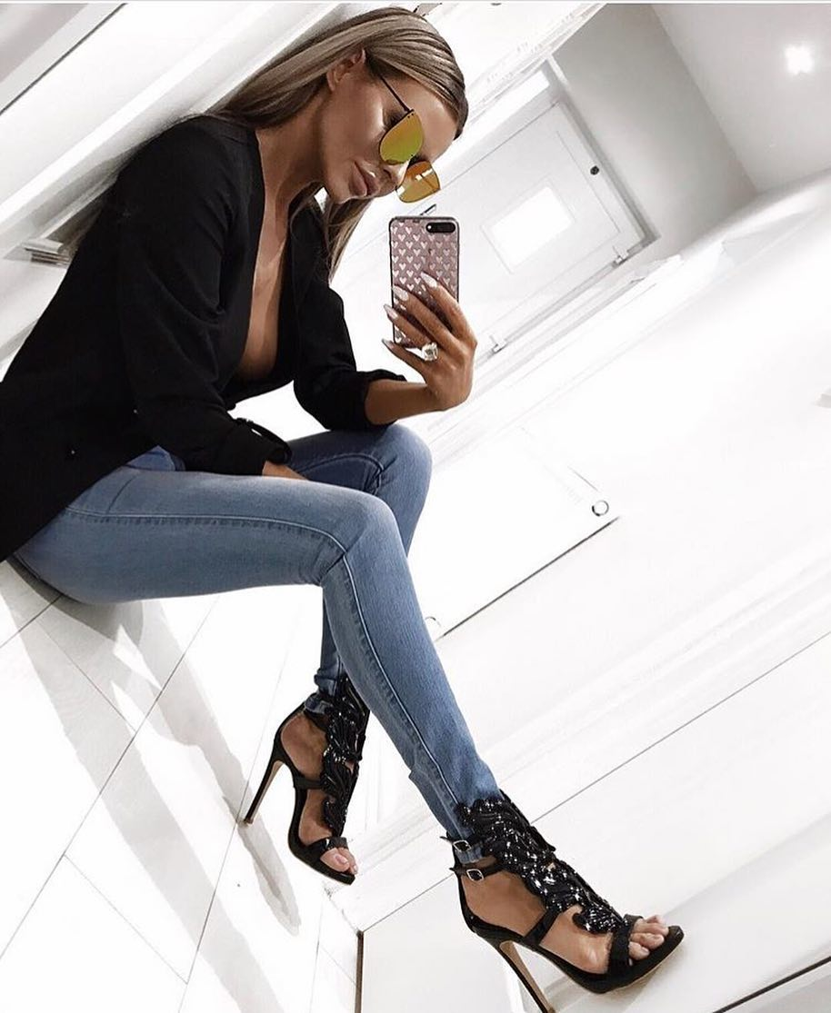 Black Shirt With Deep Cleavage And Wash Blue Jeans With Black Leaf Sandals 2020